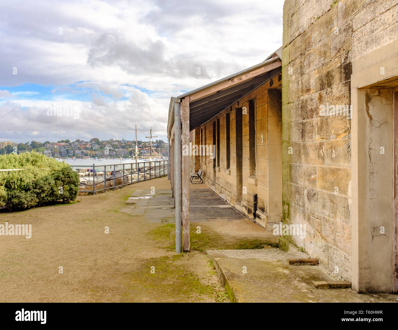 Cockatoo island Sydney, Australia, Historical stone prison building built by convicts for solitary confinement of prisoners, tall sailing ships masts  - Stock Image