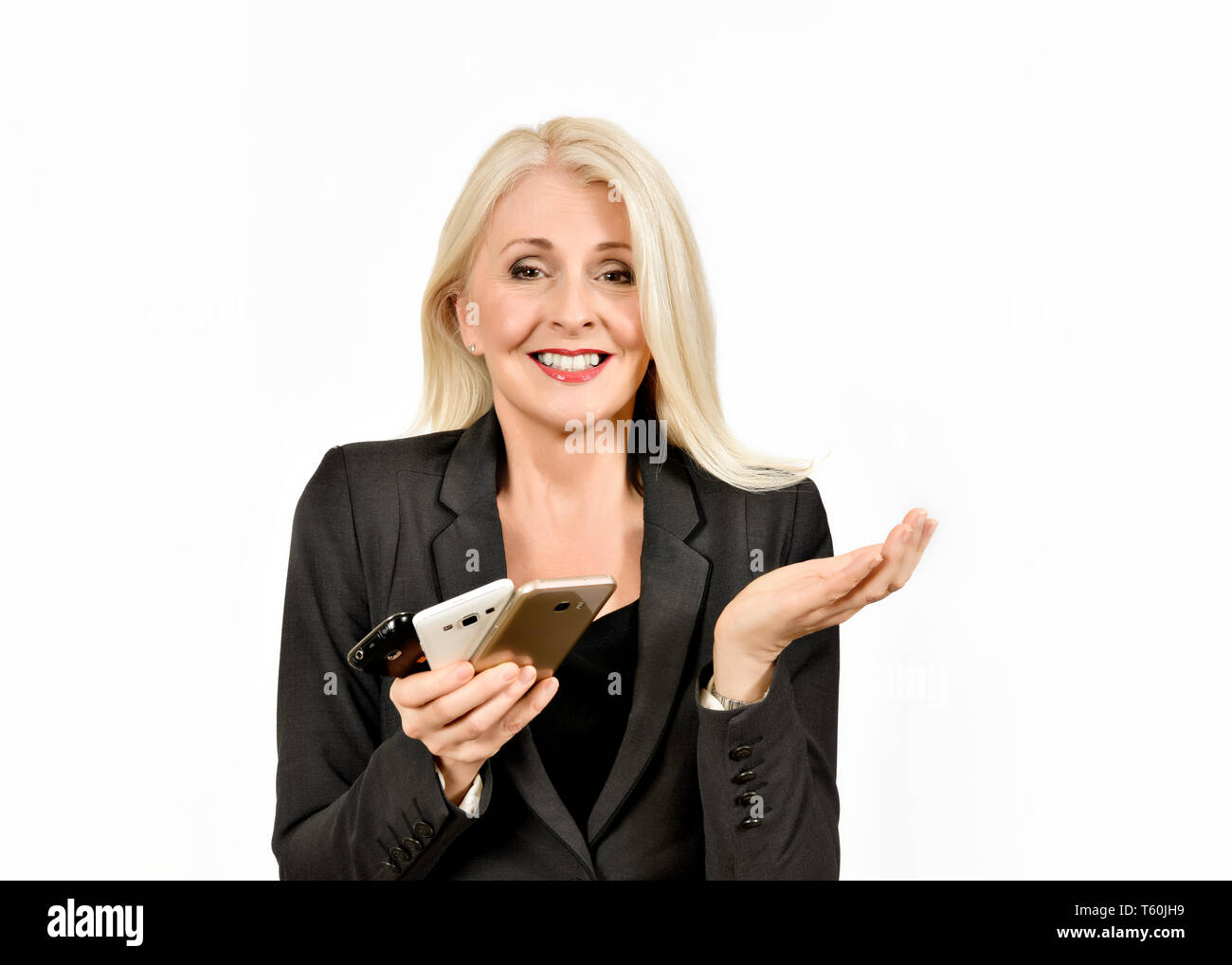 Attractive business woman holding multiple mobile phones with hand up in  a resigned look Stock Photo
