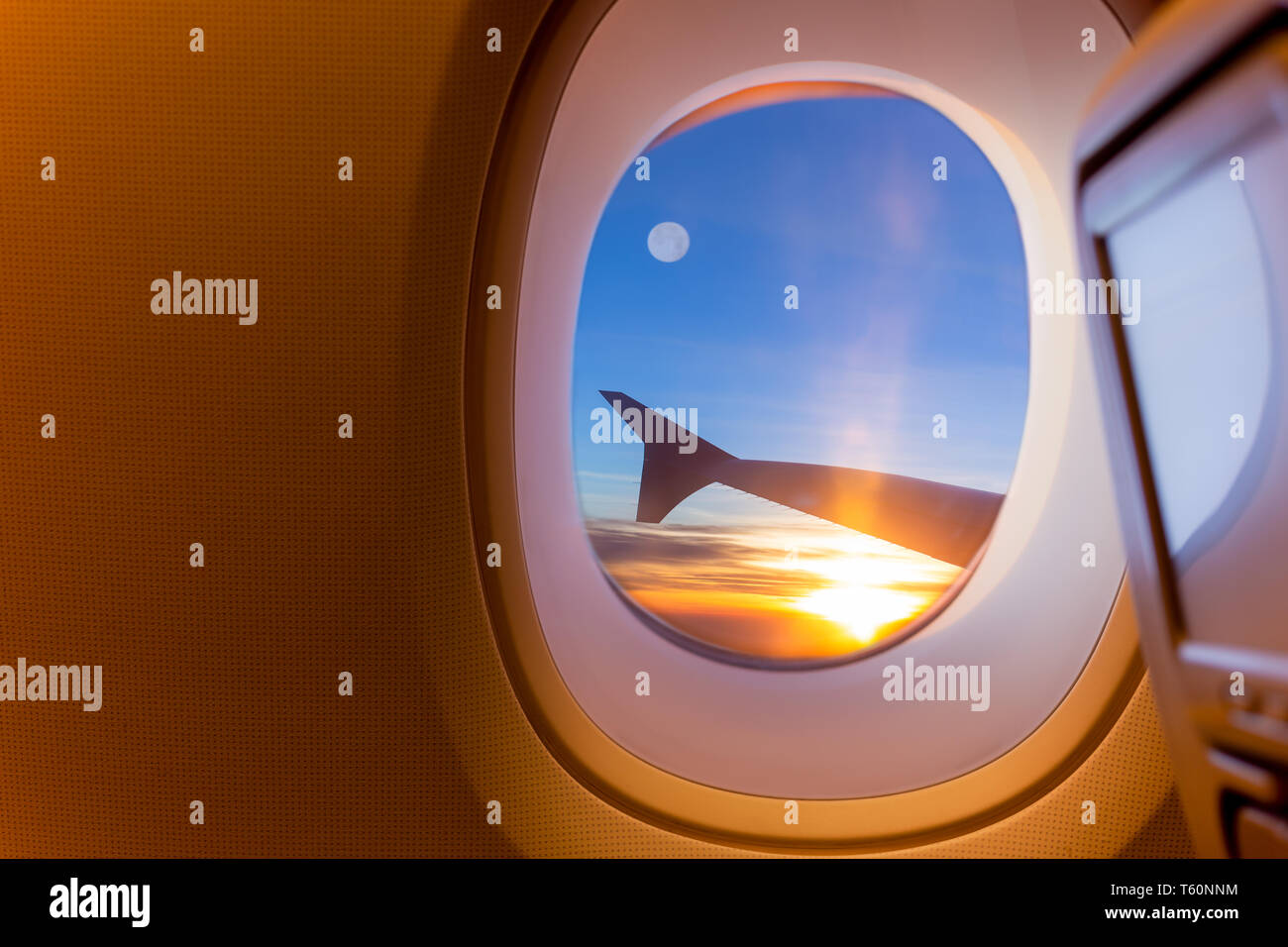 Beautiful scenic of sunrise and fullmoon through the aircraft window. - Stock Image