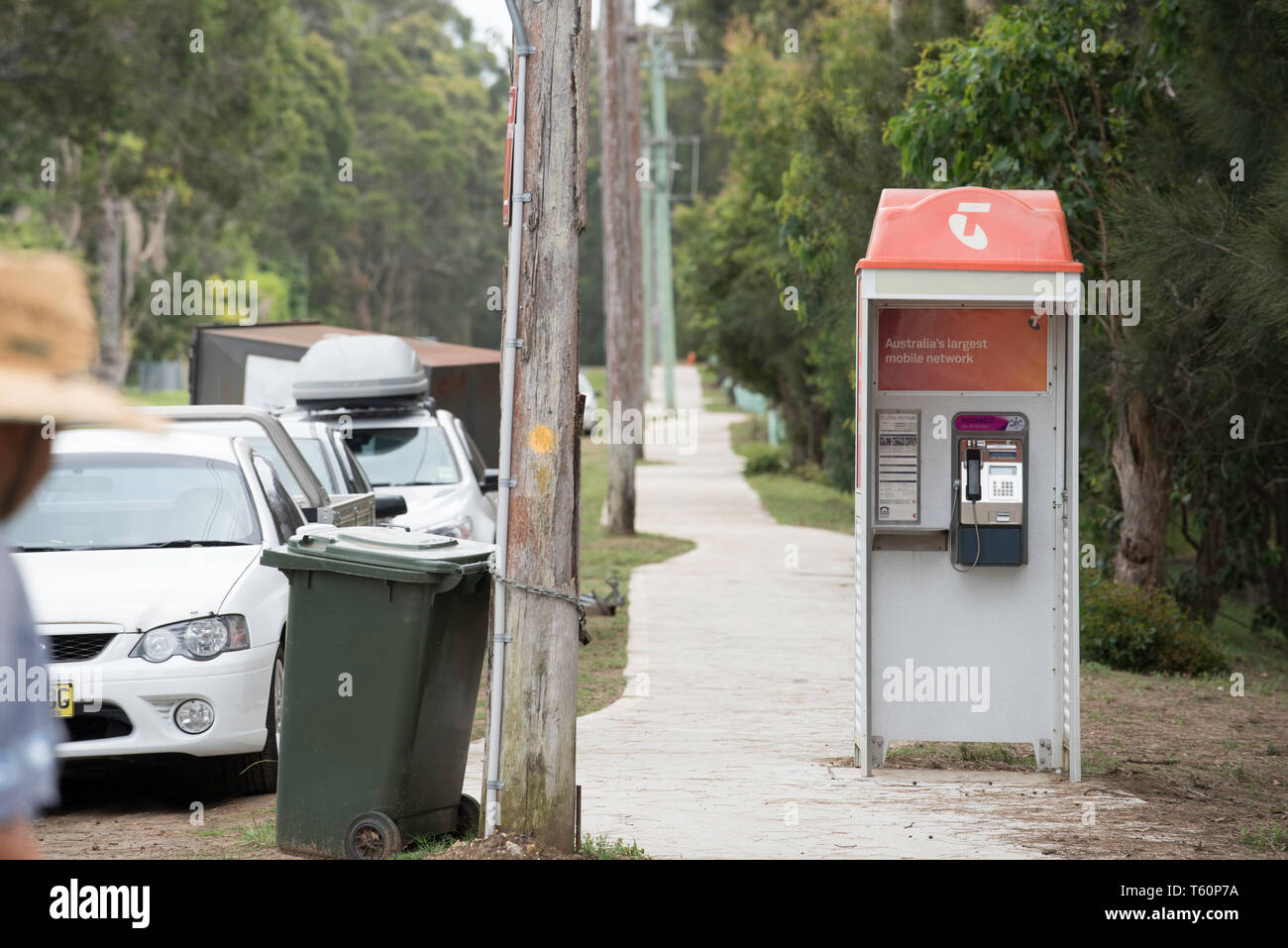 Kioloa, New South Wales, Australia: A traditional Telstra phone booth on a footpath in a rural village now almost redundant due to mobile, cell phones - Stock Image