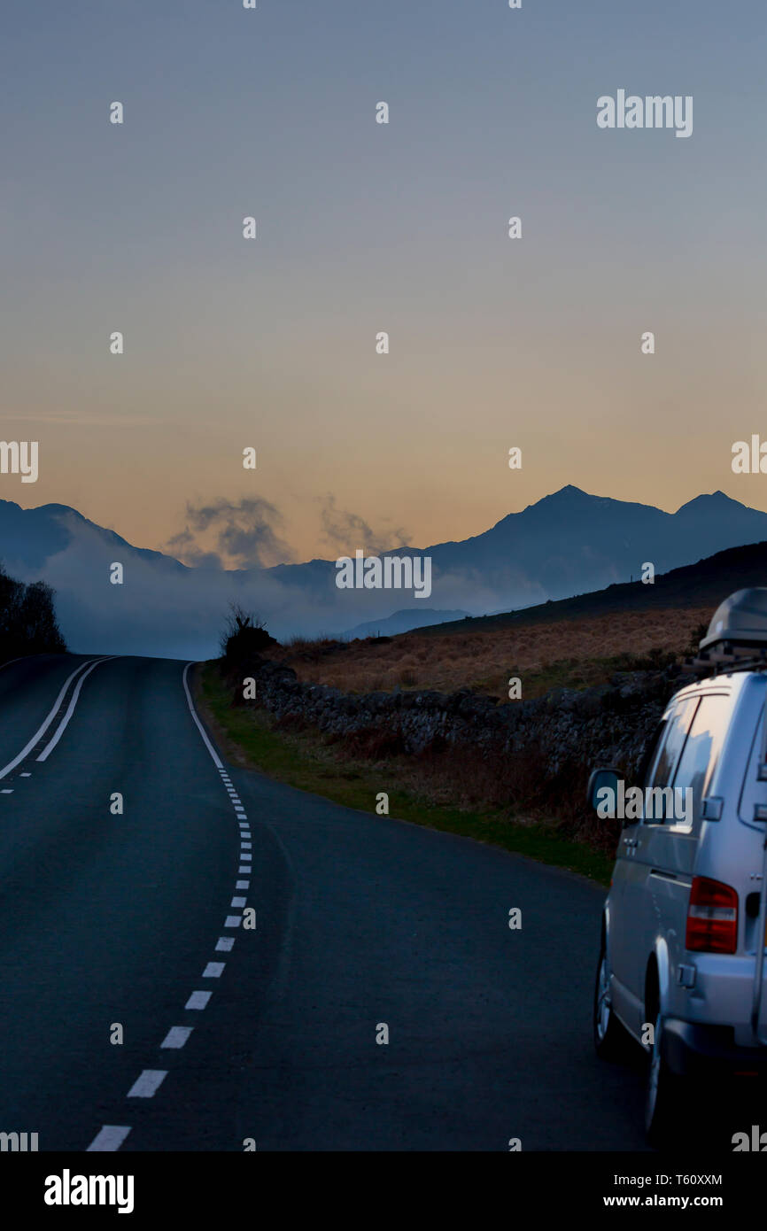 Campervan parked in layby as driver stops to photograph the scenic, twilight view of Mount Snowdon at dusk, Snowdonia National Park, North Wales, UK. Stock Photo