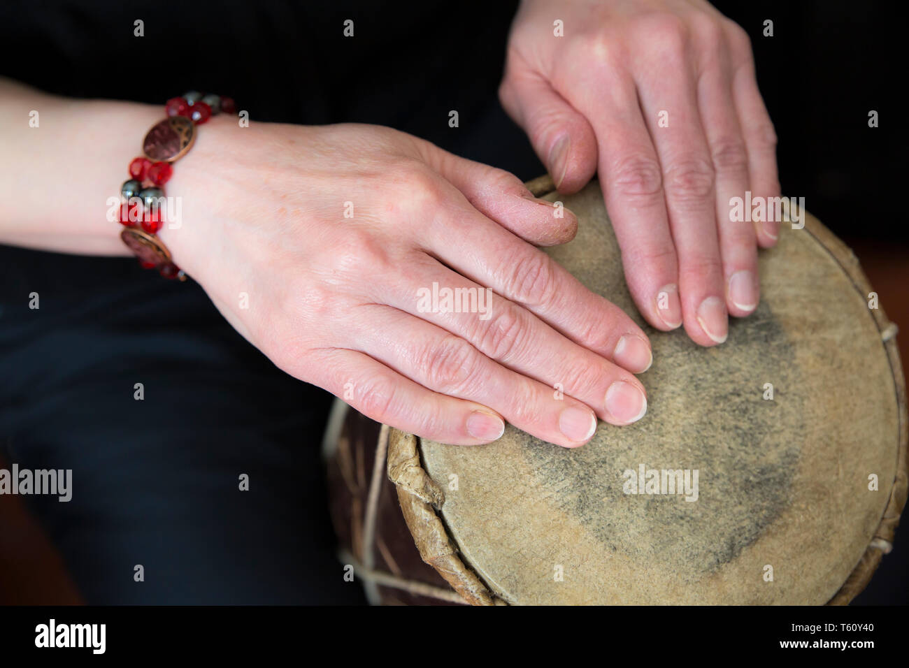 Close up of female hands playing simple, traditional African hand drum (tapping rhythm with finger tips) both hands resting on natural skin drum head. - Stock Image