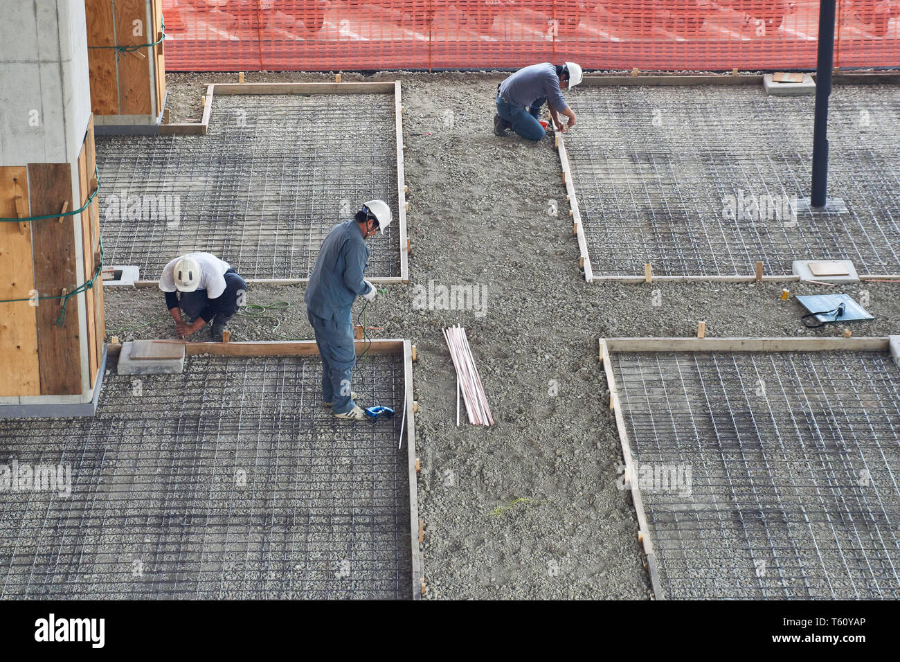 Construction workers prepare frames for pouring concrete at a bicycle parking area underneath Tsukuba Express Moriya Station in Ibaraki, Japan. - Stock Image