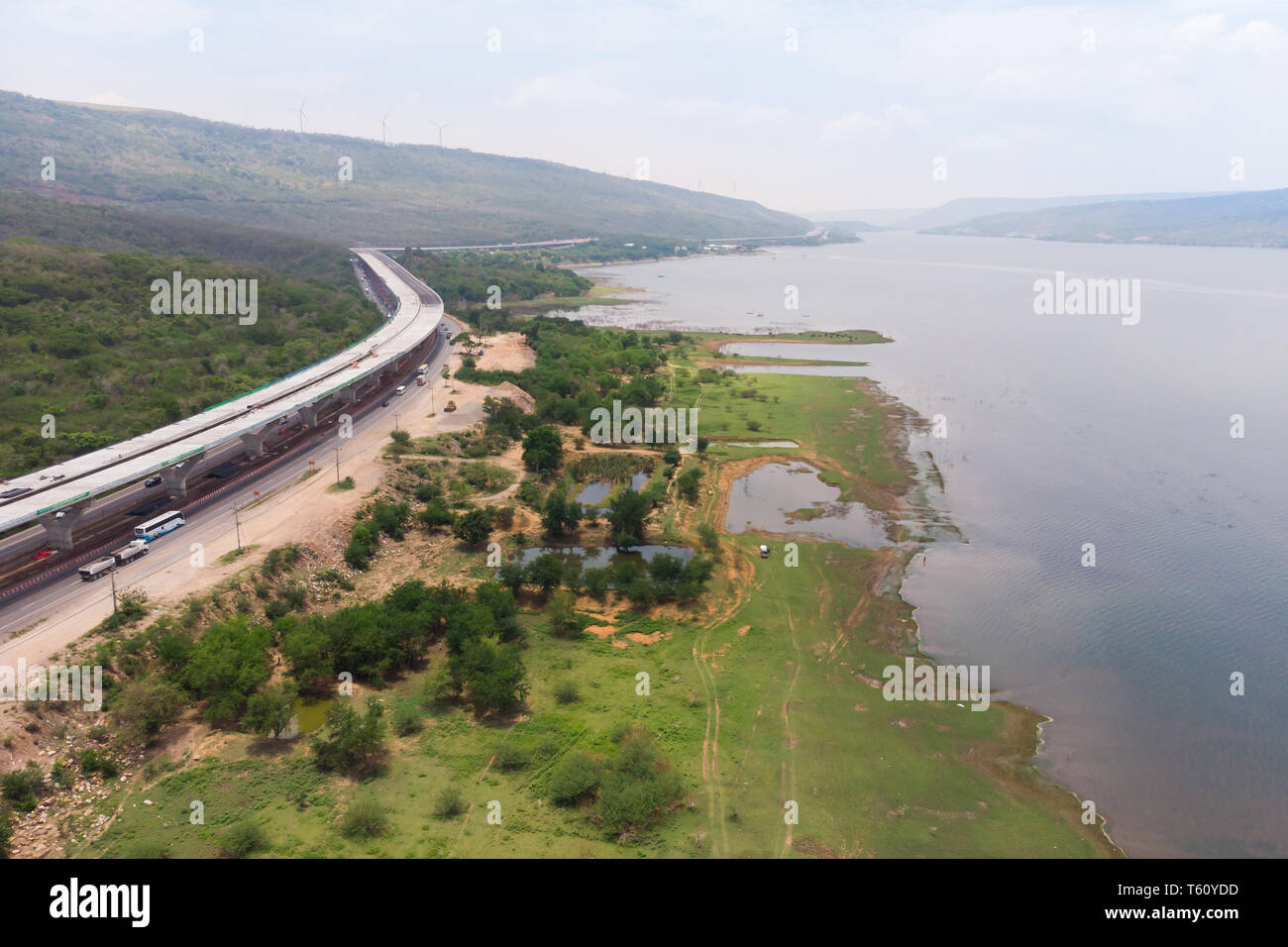 Drone shot aerial view landscape of under construction motorway tolls near big natural river - Stock Image