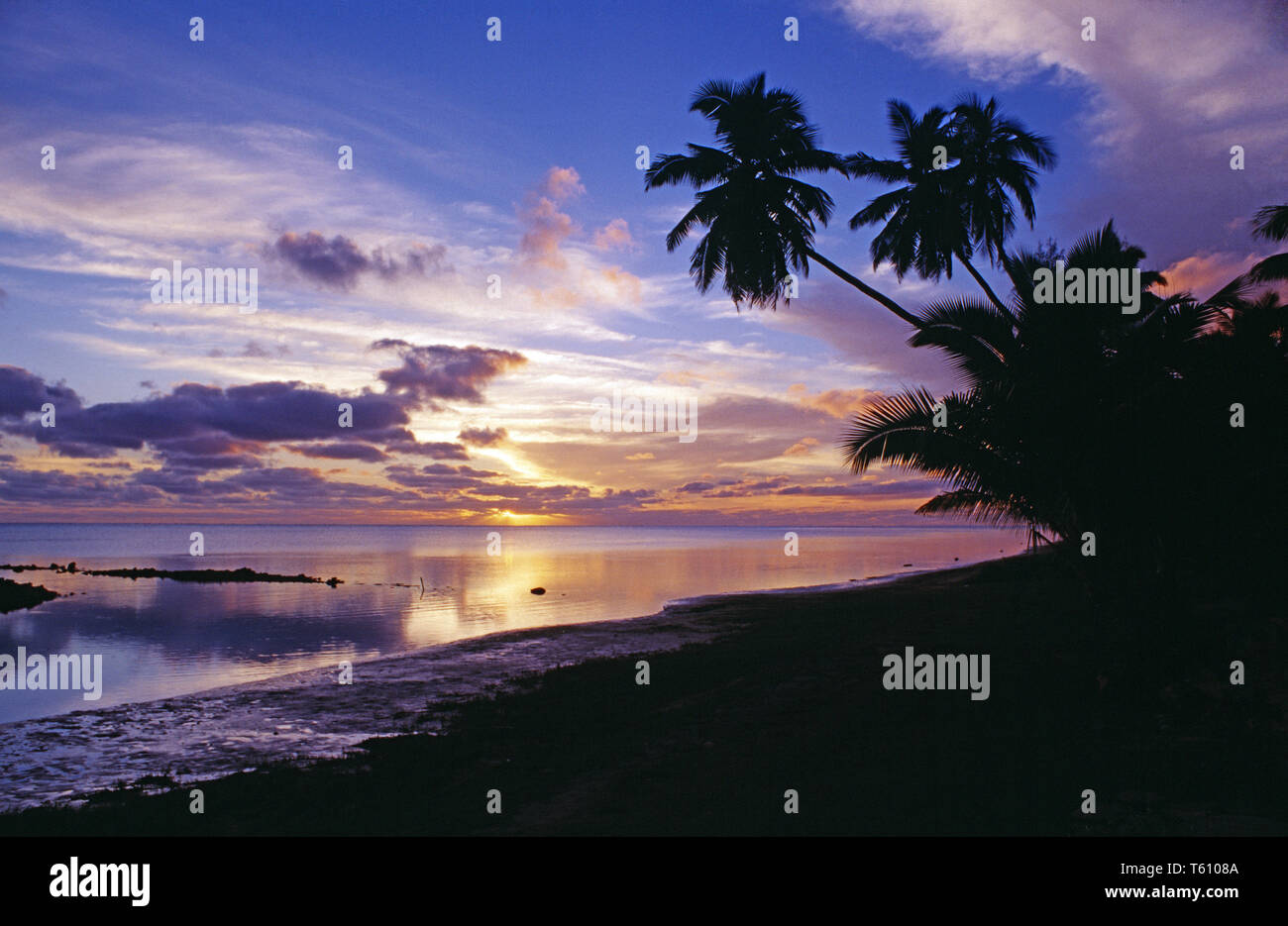 Cook Islands. Aitutaki. Tropical beach sunset with coconut palm trees. - Stock Image