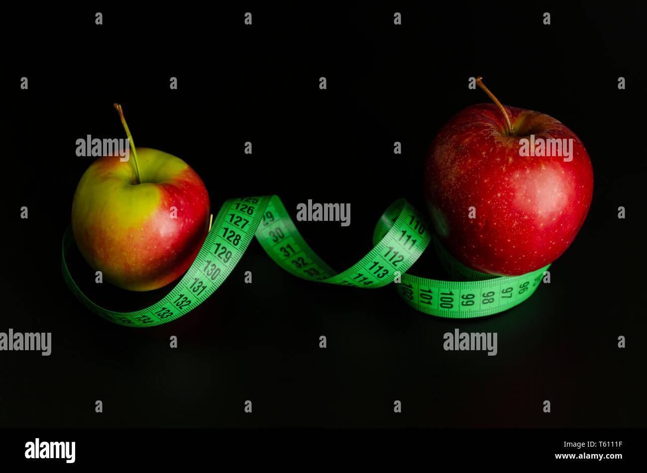 Red apple and green measuring tape on black background. Weight loss and slimming treatment concept. Copy space - Stock Image