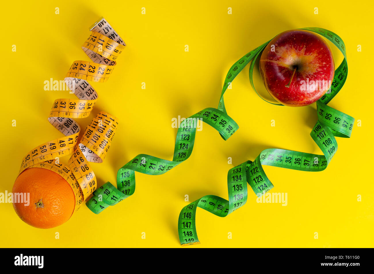 Red apple and orange with measuring tapes on yellow background. Weight loss and slimming treatment concept. Space for text - Stock Image