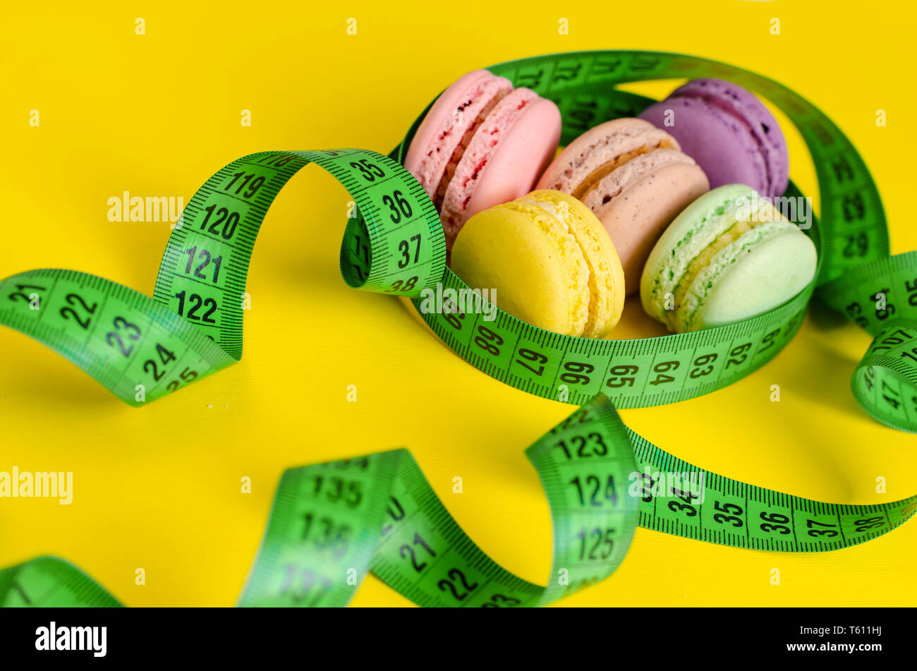 Green measuring tape and macarons or macaroons on yellow background. Weight loss and slimming treatment concept. Top view - Stock Image