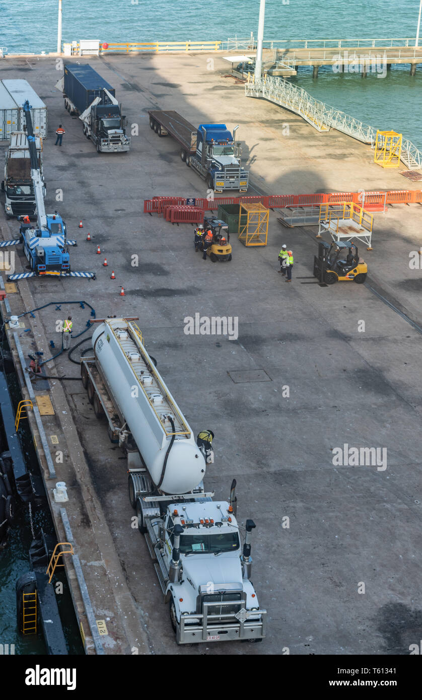 Darwin Australia - February 22, 2019: Gray tanker truck parked along ship is refueling the vessel. Other trucks and people on the dock. - Stock Image