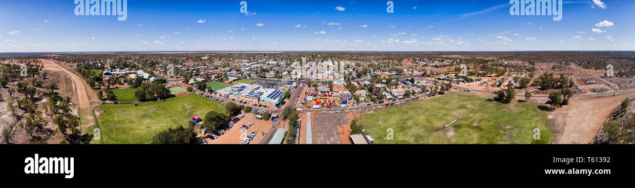 Flat plains of Australian outback with red soil and Lightning ridge remote opal mine town under blue sky in wide aerial panorama over town streets and - Stock Image