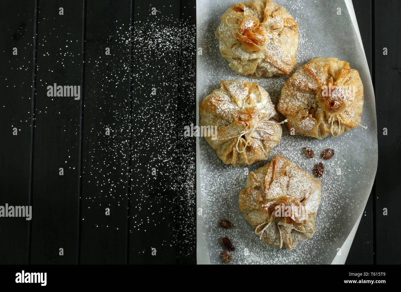 Phyllo pastry strudel with apple filling and sultana grapes, dusted with icing sugar Stock Photo