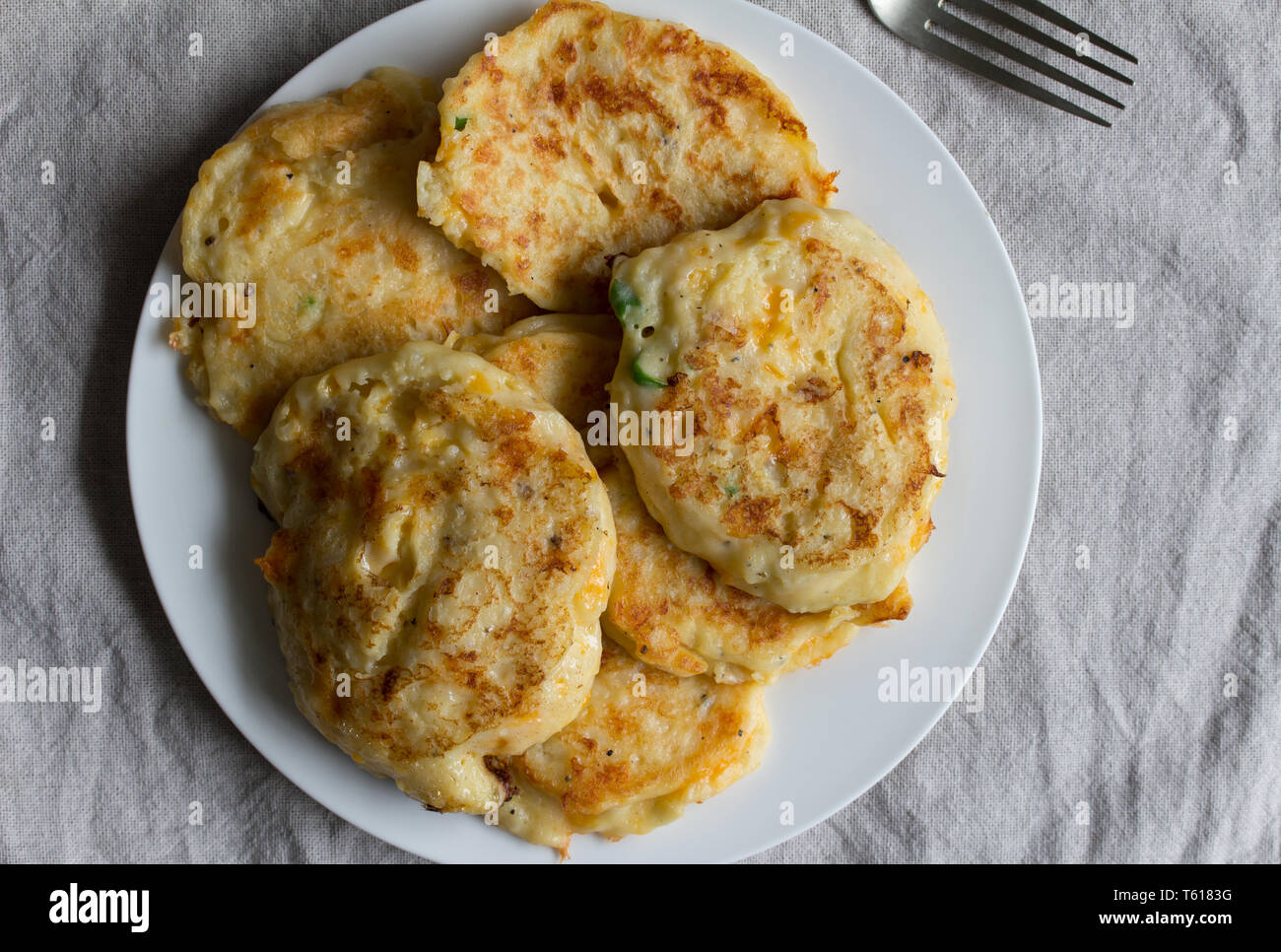 Potato pan cakes on white plate - Top view of cheesy hash browns - Stock Image
