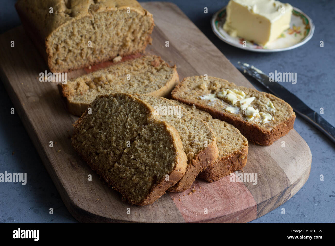 Banana bread loaf with slices and butter  on wooden board on grey background Stock Photo