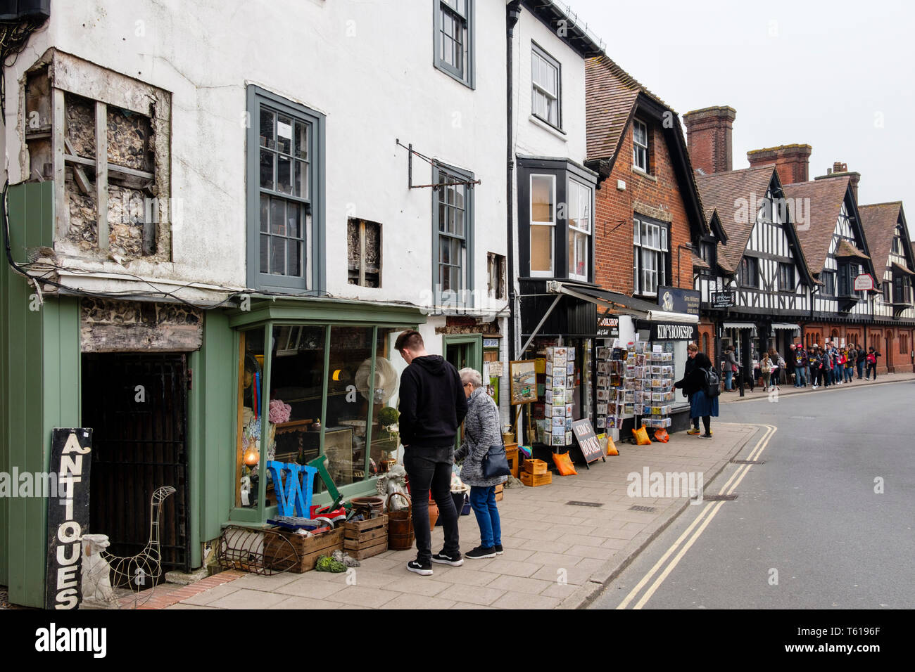 Shopers looking at antique junk items for sale outside an old Antiques shop in the High Street, Arundel, West Sussex, England, UK, Britain Stock Photo