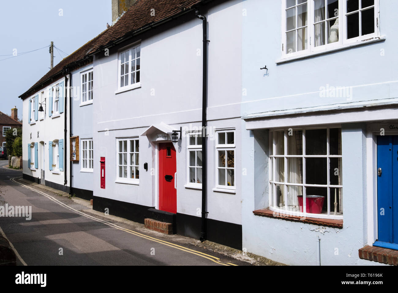 Old houses with flood defenses at front door on narrow street close to seafront. Bosham, Chichester, West Sussex, England, UK, Britain Stock Photo