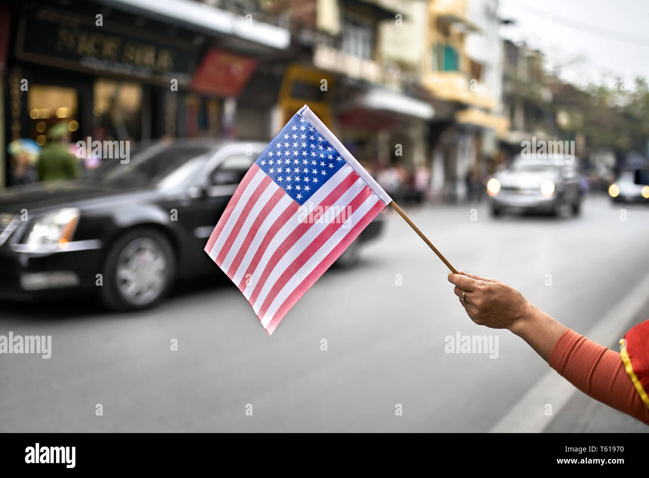 Woman's hand holds the USA flag on the blurred background of
