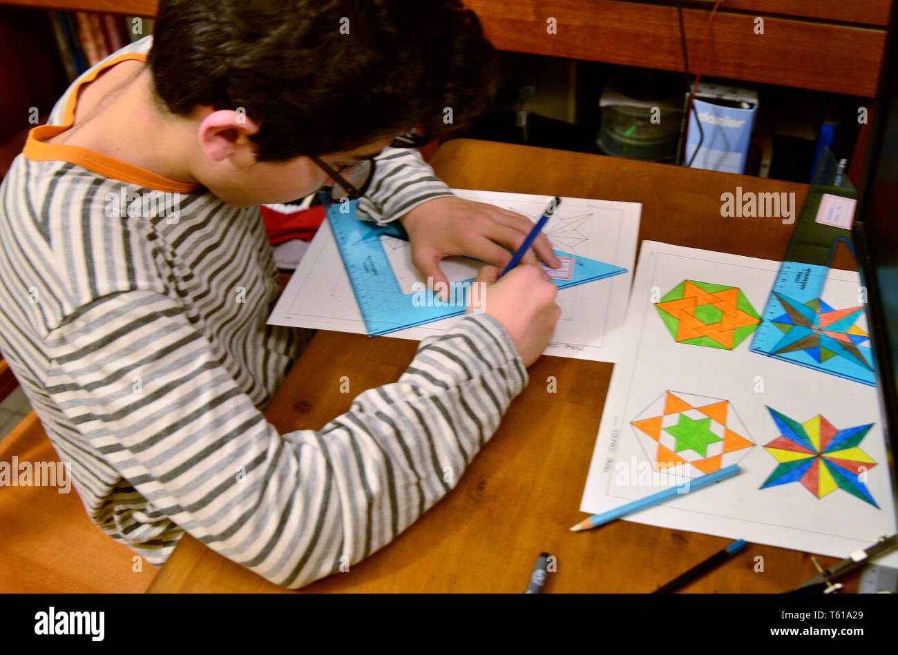 Turin, Piedmont, Italy. April 2019. A black-haired Caucasian boy with glasses does his technical drawing homework. With compass, ruler, square, it cre - Stock Image