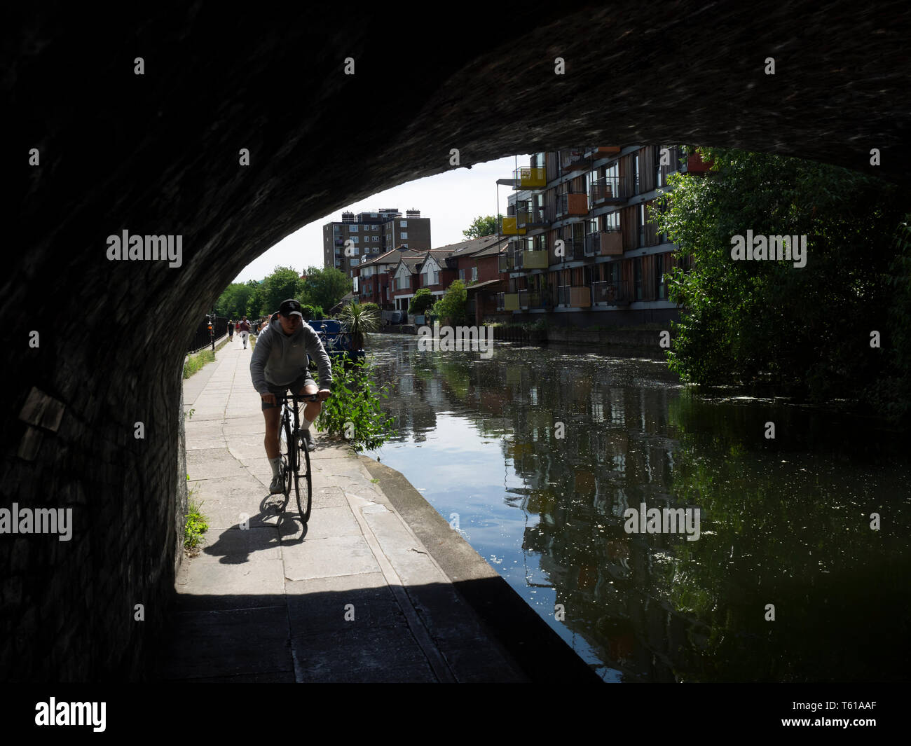 REGENT'S CANAL, LONDON:  Cyclist on Towpath under bridge - Stock Image