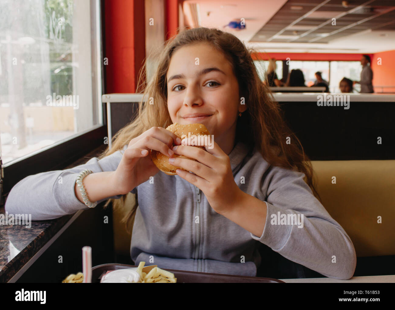 Pretty young teen girl with an appetite eating hamburger in a cafe Stock Photo