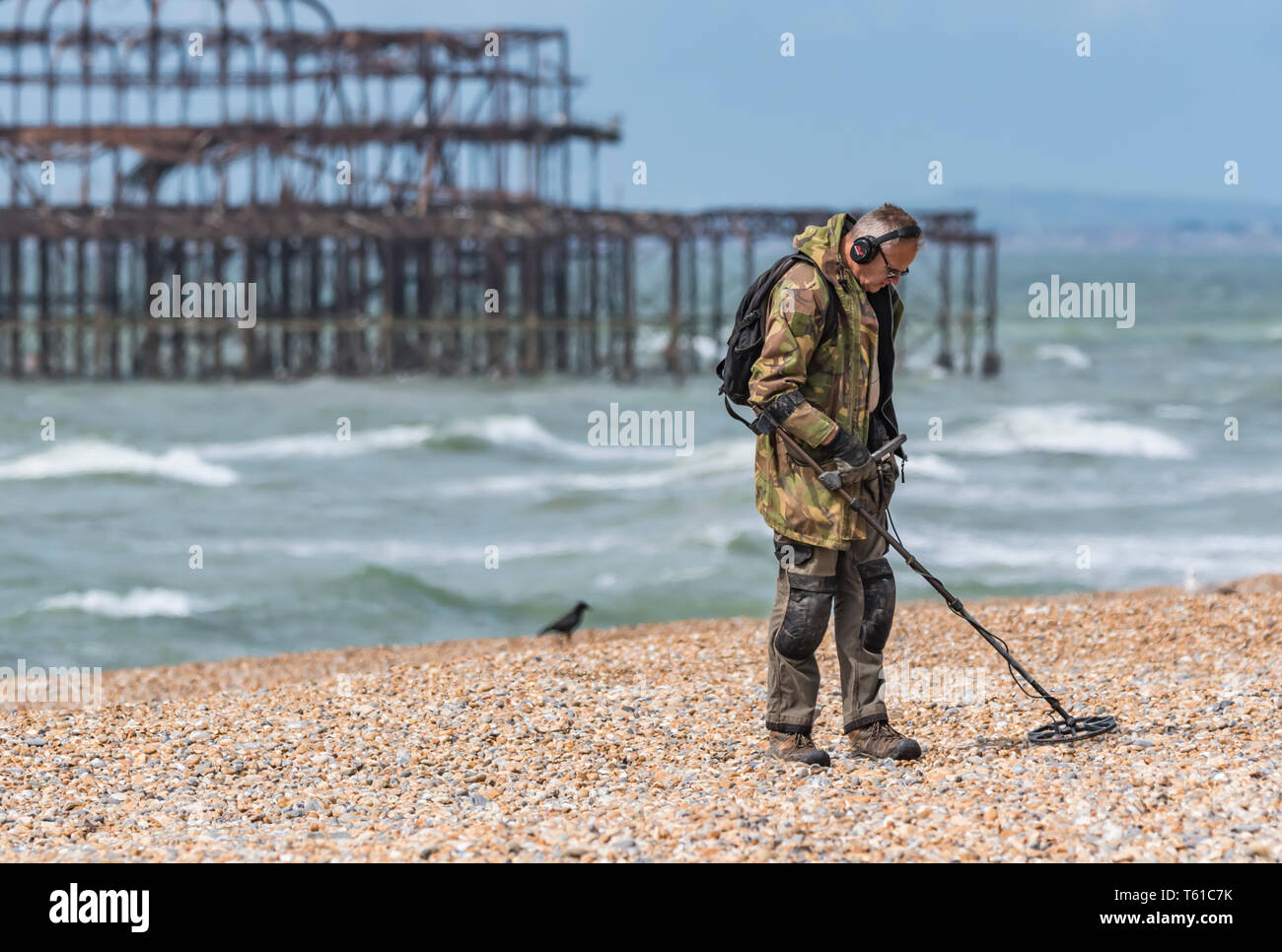 Man searching for treasure on a beach using a metal detector in Brighton, East Sussex, England, UK. - Stock Image