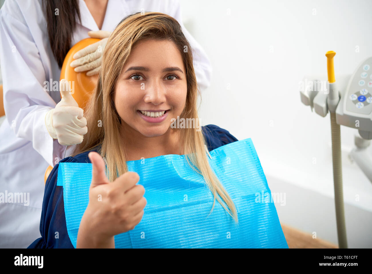 Lovely dentistry patient showing thumbs-up - Stock Image