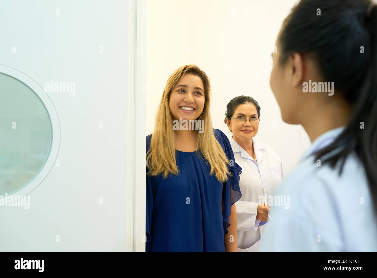 Cheerful woman entering dentistry office - Stock Image