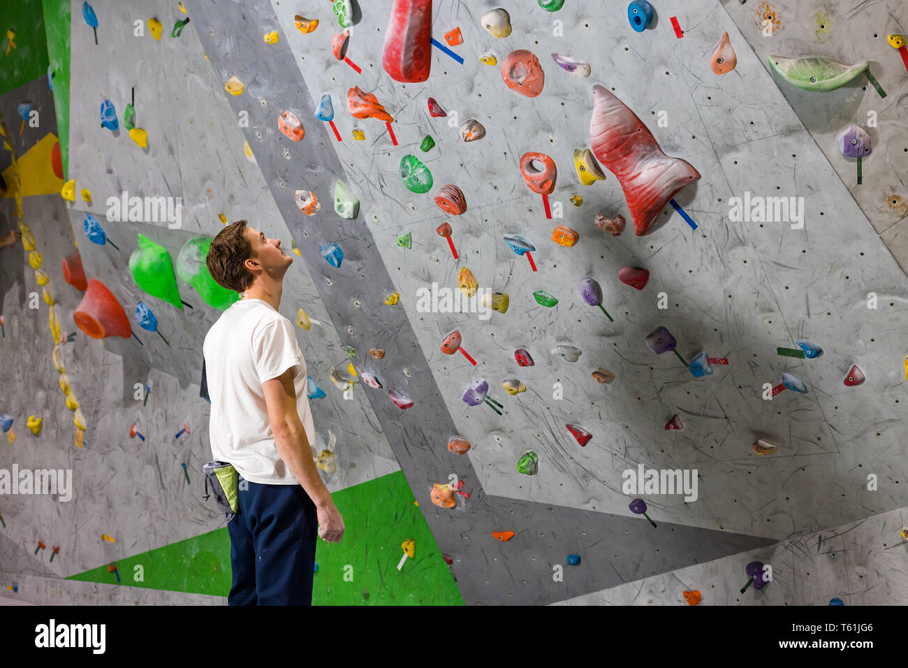 Rock climber stands and looks at the climbing wall with hooks in the boulder hall Stock Photo