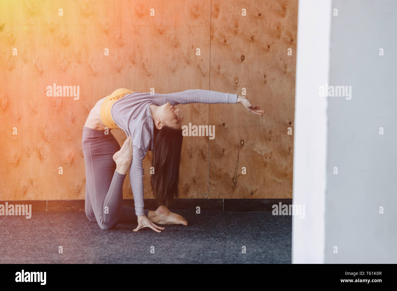Cozy young attractive girl doing fitness exercises with yoga on the floor on a wooden background at gym - Stock Image