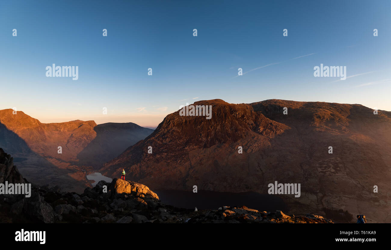 person scrambling climbing welsh mountain try fan in the early morning light - Stock Image