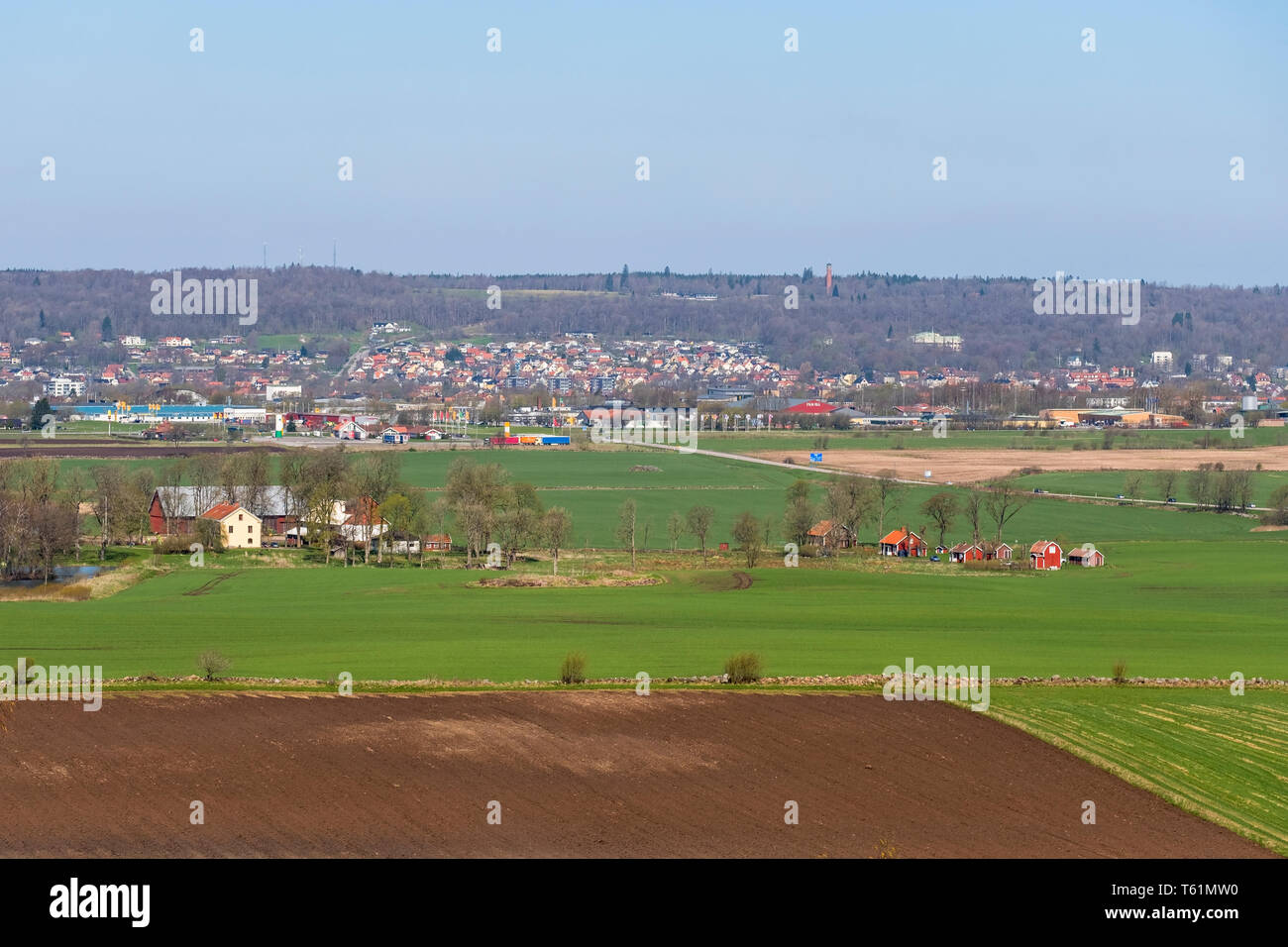 Landscape view of the fields towards a Swedish small town in the spring - Stock Image