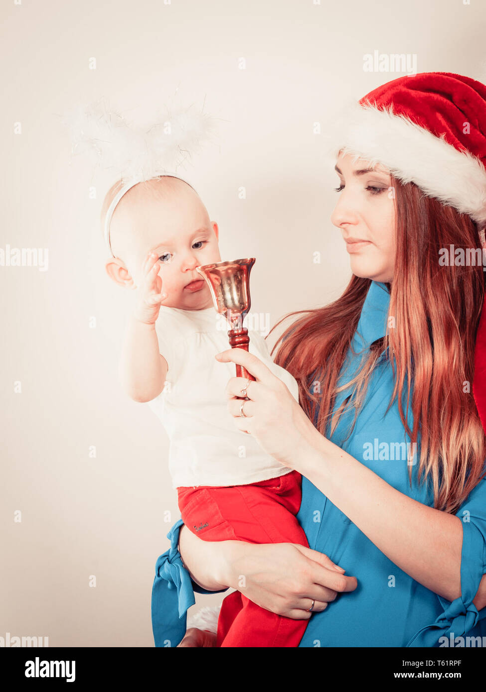 81e5b2928 Christmas woman with cute baby. Beautiful lady has red santa claus cap.