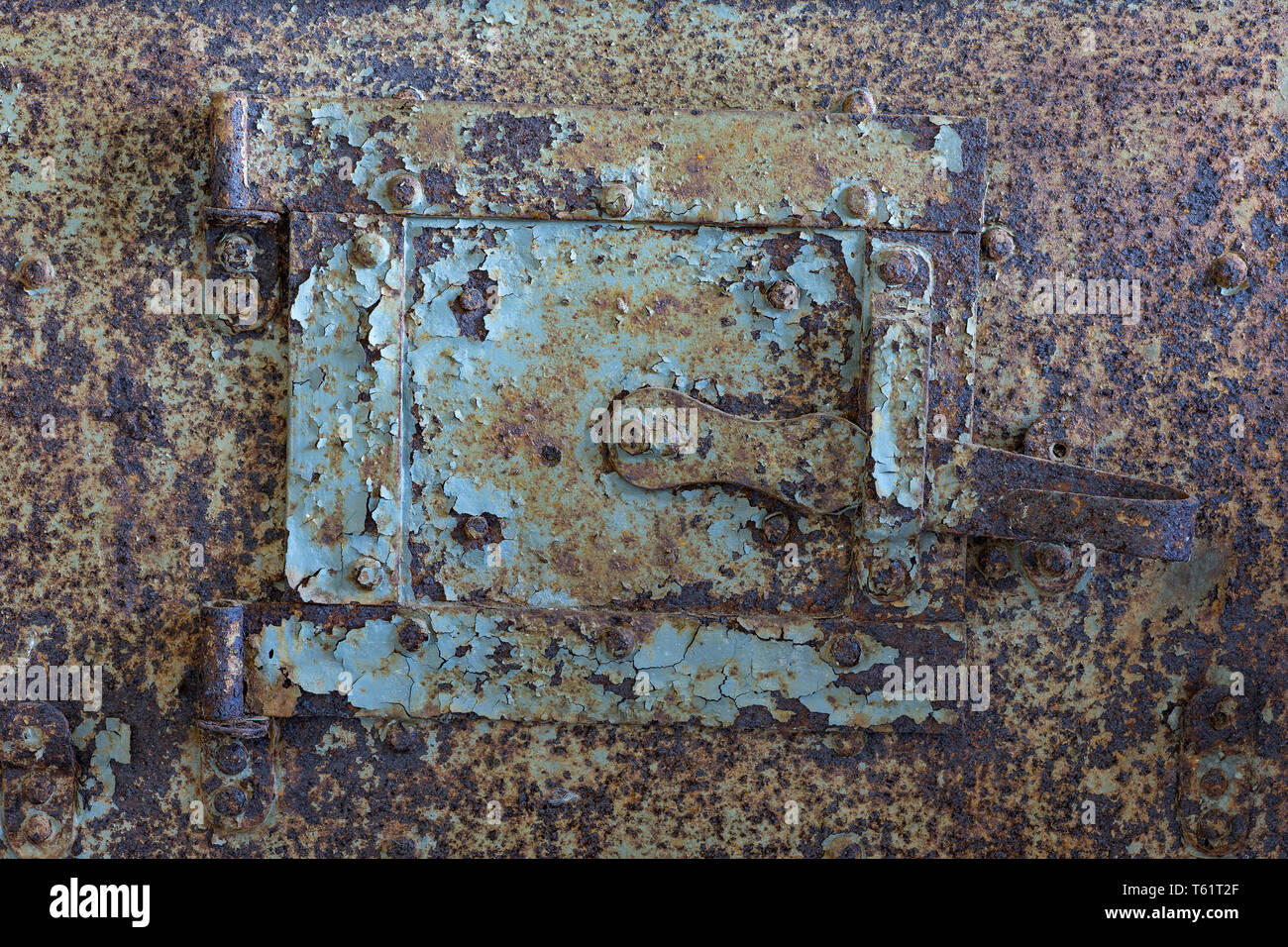 Sheet metal hatch for cleaning soot. Old rusty door with old layers of paint. - Stock Image