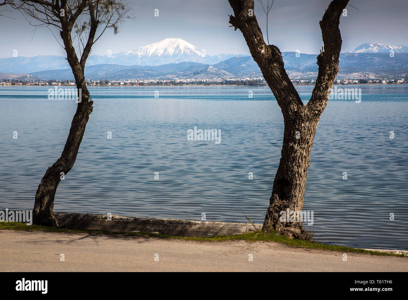 Seen from Avlida's road by the sea,Mount Olympus, traditionally known as the home of the ancient Greek gods, thrusts its snowy peak over the horizon. - Stock Image