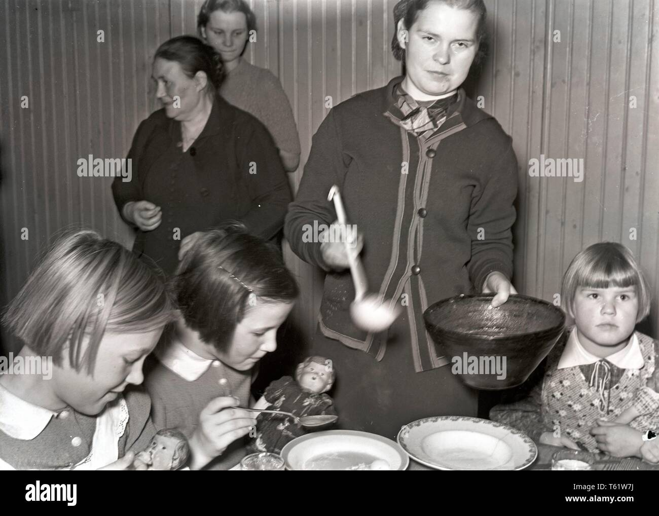 The Winter War. A military conflict between the Soviet union and Finland. It began with a Soviet invasion on november 1939 when Soviet infantery crossed the border on the Karelian Isthmus. Here a group of Finnish children being served food. Although they must experience a horrible time they play with their dolls. Photo Kristoffersson ref 98-16 January 1940 - Stock Image