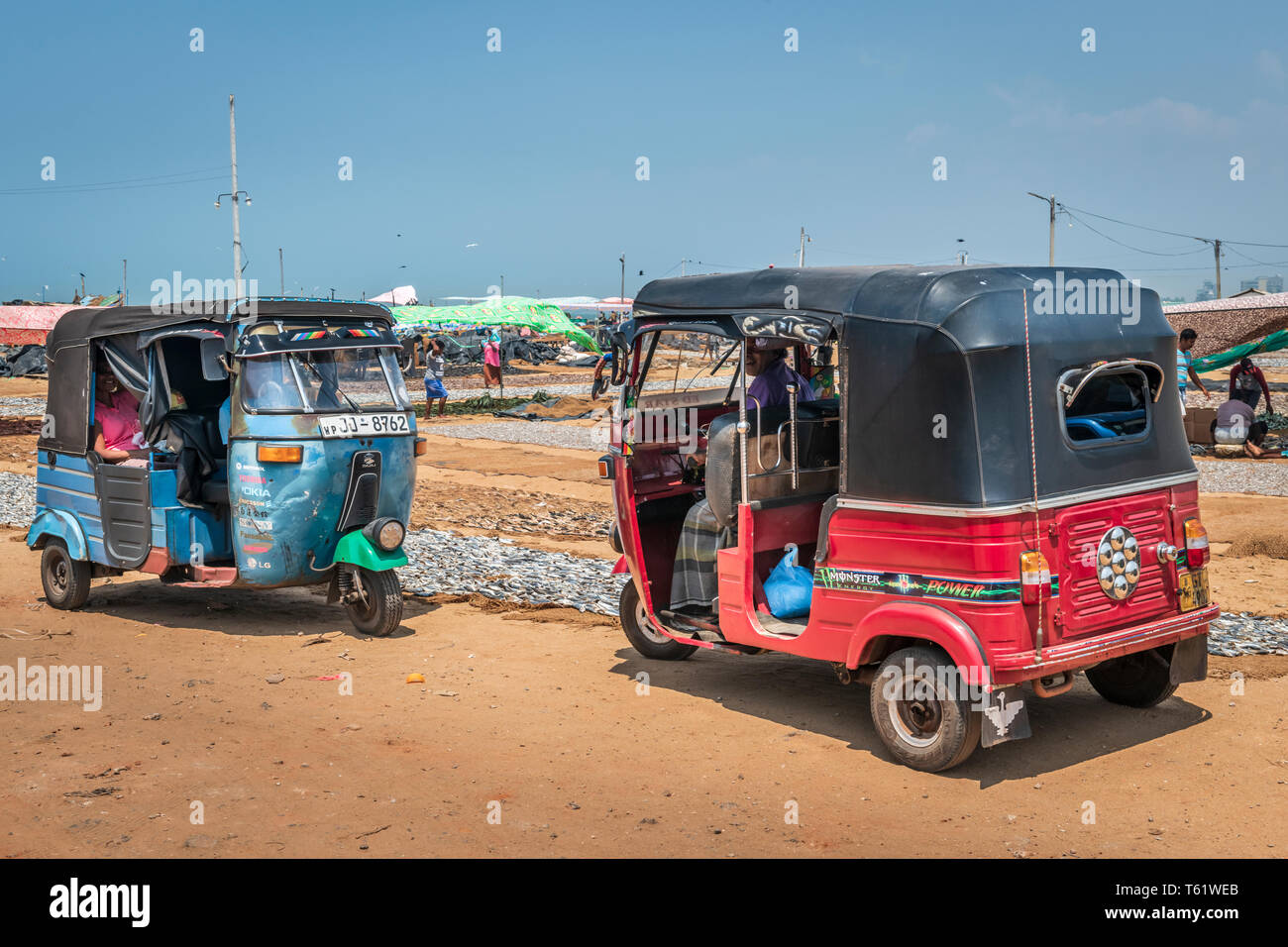 Two tuk tuks motorised rickshaws wait for customers at the famous negombo fish market