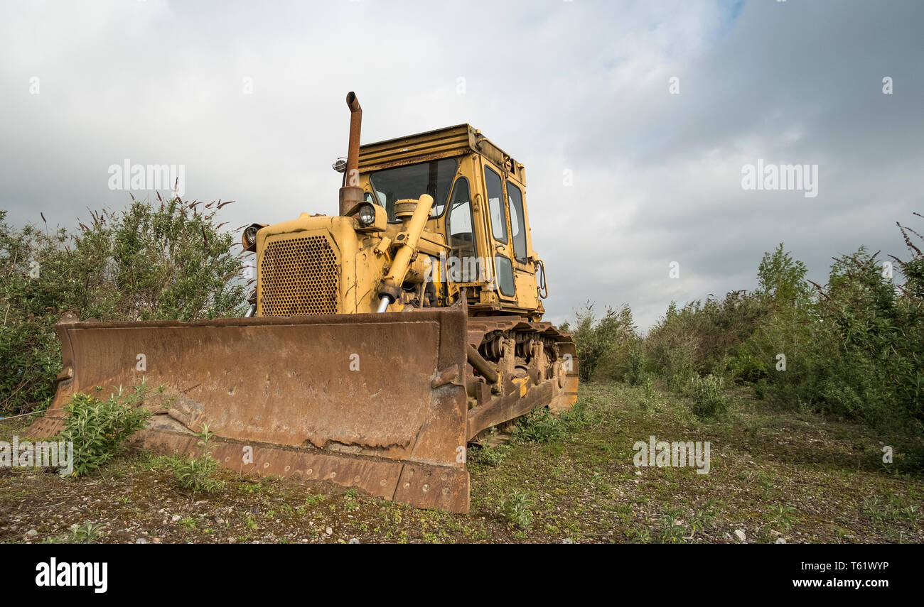 Old yellow bulldozer standing idle - Stock Image