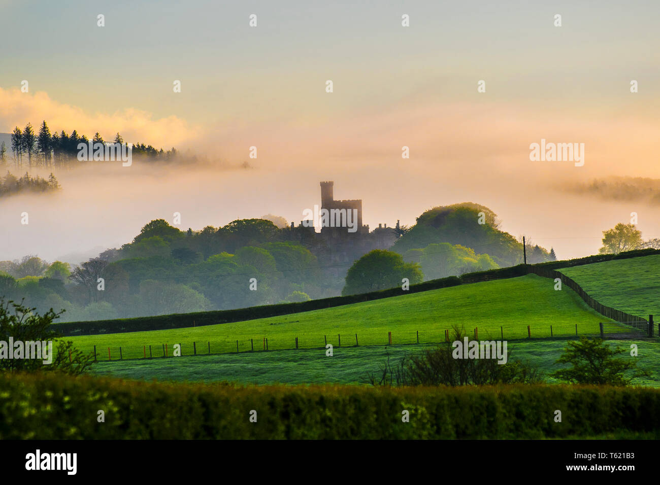 Hornby, Lancaster, UK. 28th April, 2019. UK Weather. Misty, damp hazy morning over Hornby Castle and the limed fields of rural Lancashire. Hornby Castle is a country house, developed from a medieval castle, standing to the east of the village of Hornby in the Lune Valley, Lancashire. It occupies a position overlooking the village in a curve of the River Wenning. Credit: Media World Images/Alamy Live News - Stock Image
