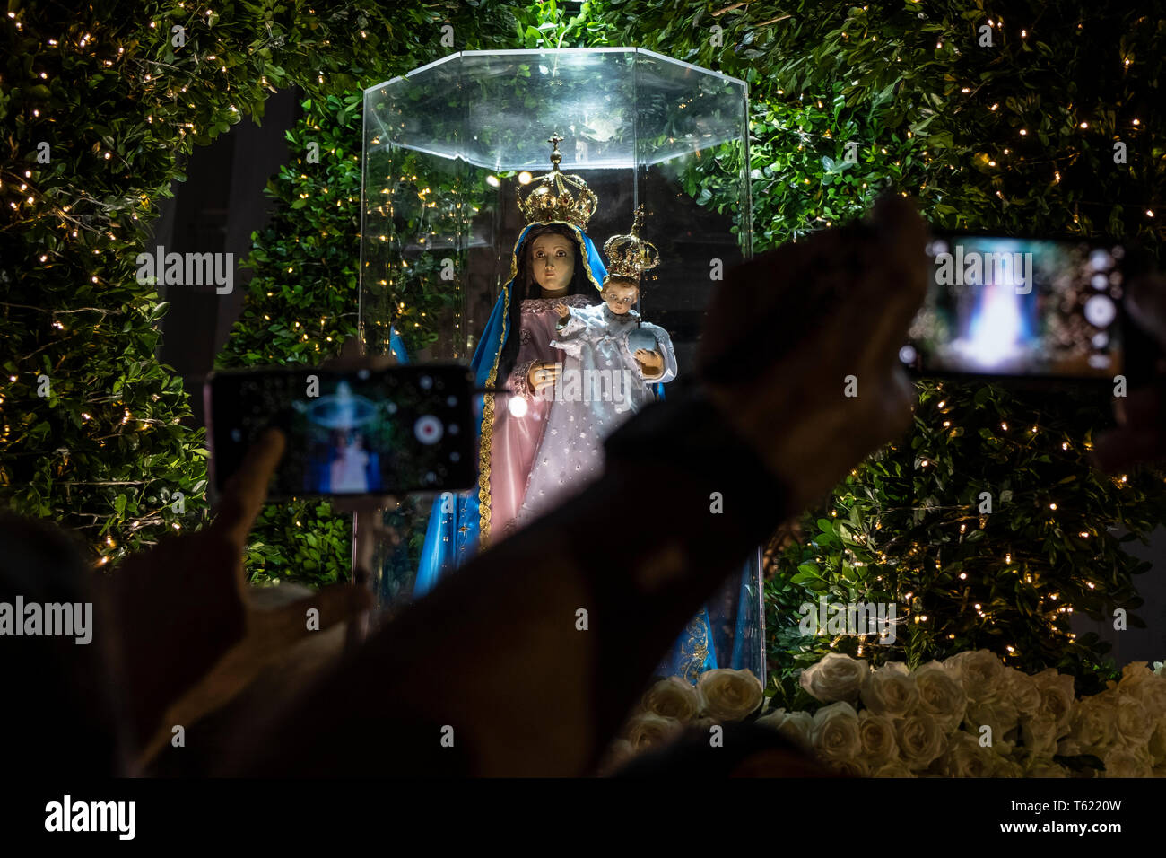 dpatop - 27 April 2019, Brazil, Vitória do Espírito Santo: Believers film the figure of the Virgin Nuestra Señora de la Penha before the pilgrimage in the city of Vitória do Espírito Santo in southeast Brazil. The 'Romería de los hombres' (men's pilgrimage) is a pilgrimage of Catholic believers that has been celebrated every year since 1958. The pilgrimage is considered one of the three largest in Brazil. According to the Catholic Church, about 700,000 people attended the event this year. Photo: Diego Herculano/dpa - Stock Image