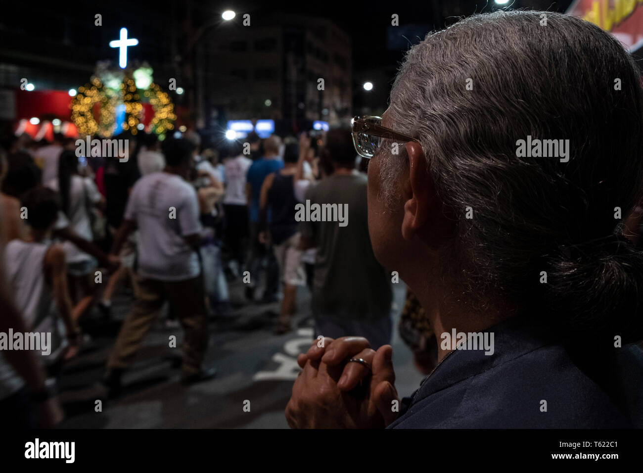 27 April 2019, Brazil, Vitória do Espírito Santo: A believer prays during the pilgrimage in the city of Vitória do Espírito Santo in the southeast of Brazil. The 'Romería de los hombres' (men's pilgrimage) is a pilgrimage of Catholic believers that has been celebrated every year since 1958. The pilgrimage is considered one of the three largest in Brazil. According to the Catholic Church, about 700,000 people attended the event this year. Photo: Diego Herculano/dpa - Stock Image