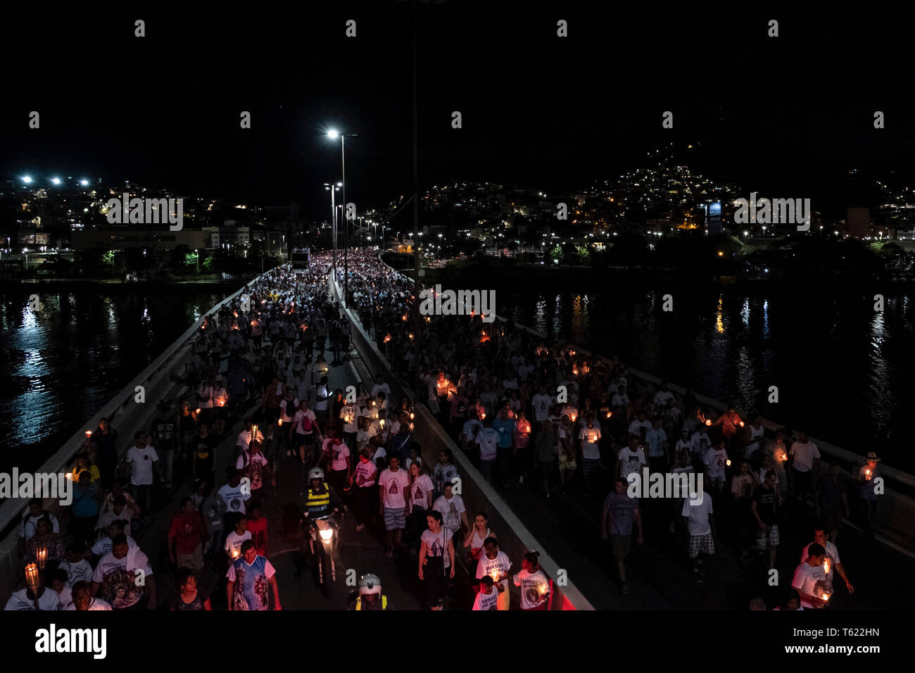 27 April 2019, Brazil, Vitória do Espírito Santo: Believers take part in the pilgrimage in the city of Vitória do Espírito Santo in the southeast of Brazil with candles. The 'Romería de los hombres' (men's pilgrimage) is a pilgrimage of Catholic believers that has been celebrated every year since 1958. The pilgrimage is considered one of the three largest in Brazil. According to the Catholic Church, about 700,000 people attended the event this year. Photo: Diego Herculano/dpa - Stock Image
