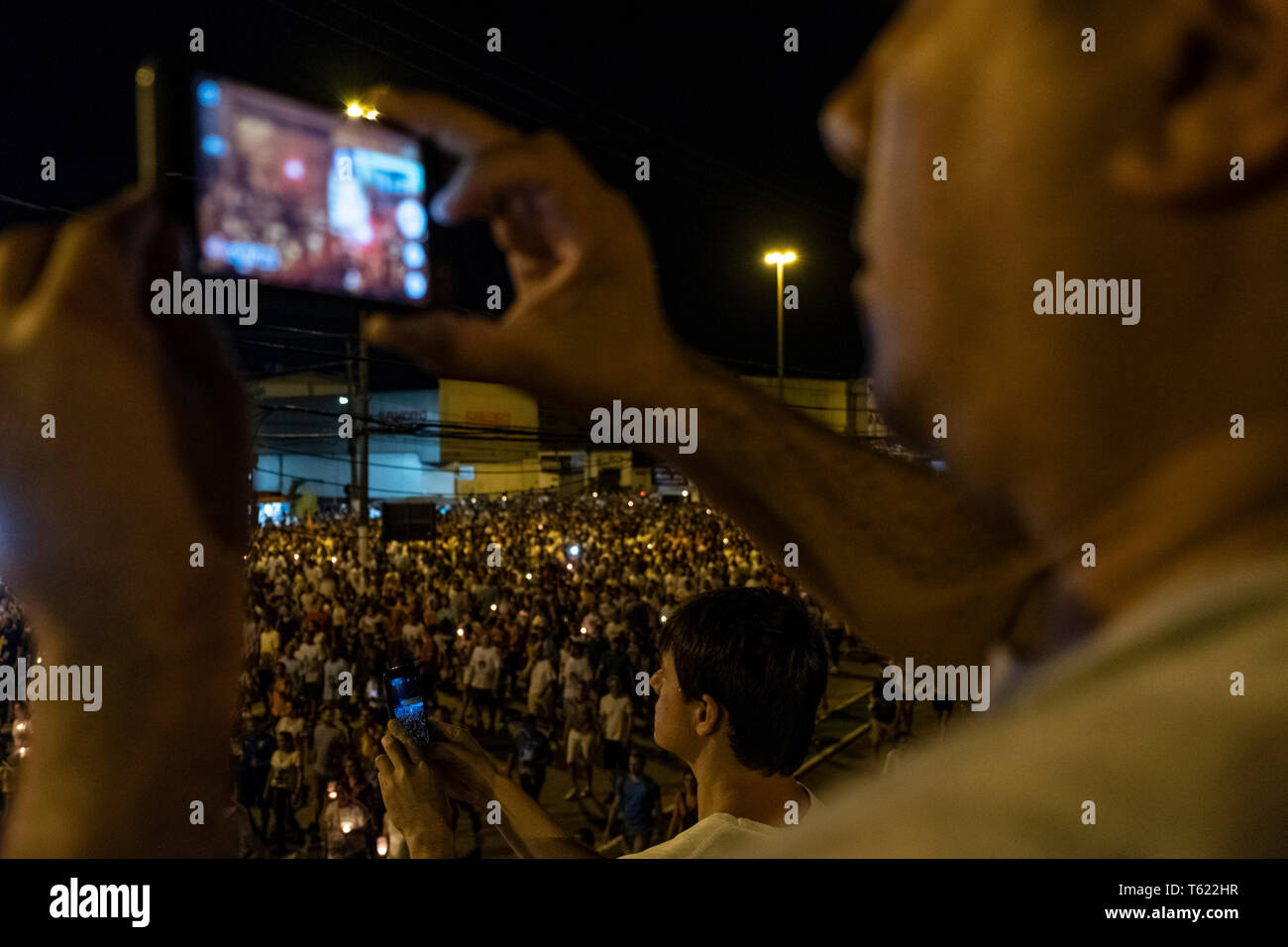 27 April 2019, Brazil, Vitória do Espírito Santo: Residents of the city film believers during the pilgrimage in the city of Vitória do Espírito Santo in southeast Brazil. The 'Romería de los hombres' (men's pilgrimage) is a pilgrimage of Catholic believers that has been celebrated every year since 1958. The pilgrimage is considered one of the three largest in Brazil. According to the Catholic Church, about 700,000 people attended the event this year. Photo: Diego Herculano/dpa - Stock Image