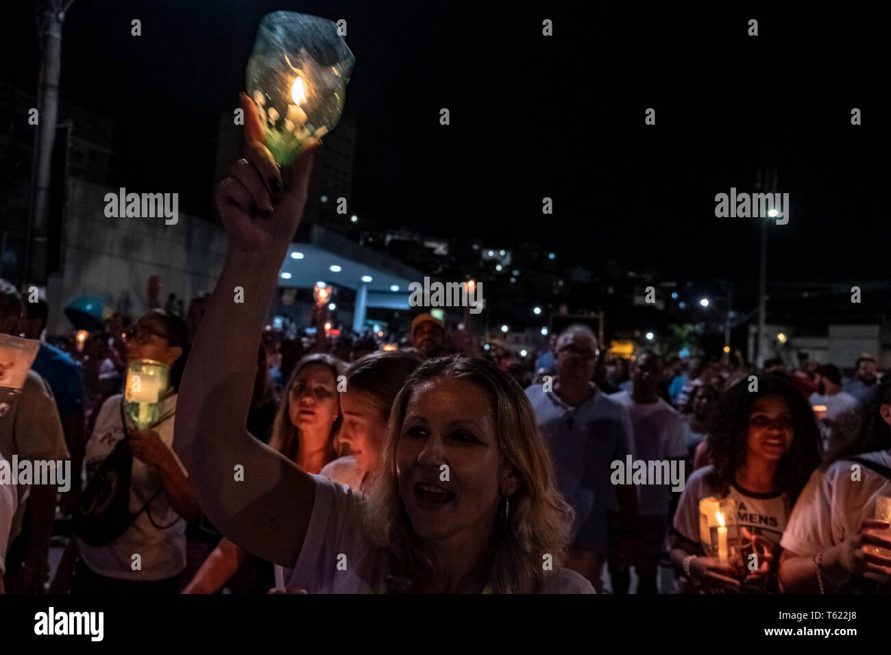 27 April 2019, Brazil, Vitória do Espírito Santo: A woman lifts a candle and sings during the pilgrimage in the city of Vitória do Espírito Santo in southeast Brazil. The 'Romería de los hombres' (men's pilgrimage) is a pilgrimage of Catholic believers that has been celebrated every year since 1958. The pilgrimage is considered one of the three largest in Brazil. According to the Catholic Church, about 700,000 people attended the event this year. Photo: Diego Herculano/dpa - Stock Image
