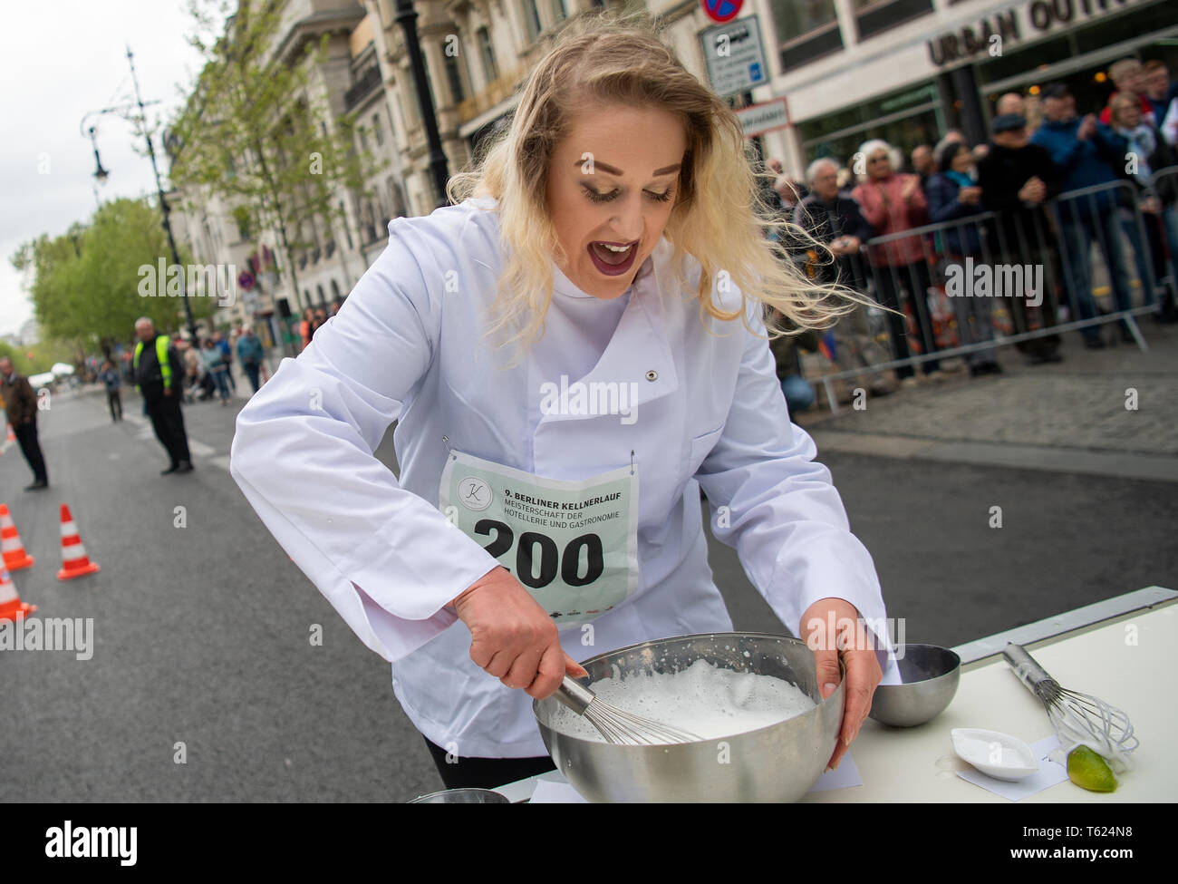 Berlin, Germany. 28th Apr, 2019. A cook beats Eischnee for a dessert at the Berliner Kellnerlauf on Kurfürstendamm. Waiters, barkeepers, chefs and bellboys compete in the art of fast gastronomy. The 400 meter long running track is located on the one-sided closed Ku'damm. Credit: Monika Skolimowska/dpa-Zentralbild/dpa/Alamy Live News Stock Photo