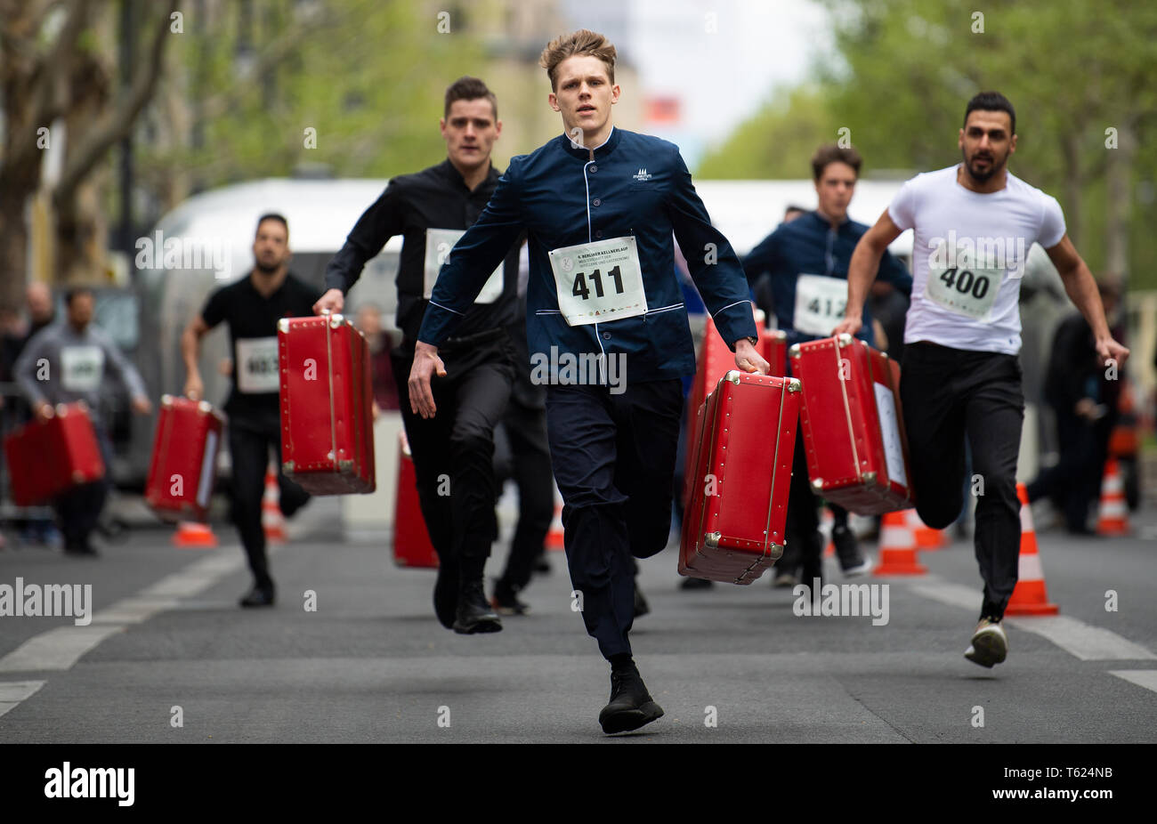 Berlin, Germany. 28th Apr, 2019. Pagen run with filled suitcases over the Kurfürstendamm at the 9th Berliner Kellnerlauf. Waiters, barkeepers, chefs and bellboys compete in the art of fast gastronomy. The 400 meter long running track is located on the one-sided closed Kudamm. Credit: Monika Skolimowska/dpa-Zentralbild/dpa/Alamy Live News Stock Photo