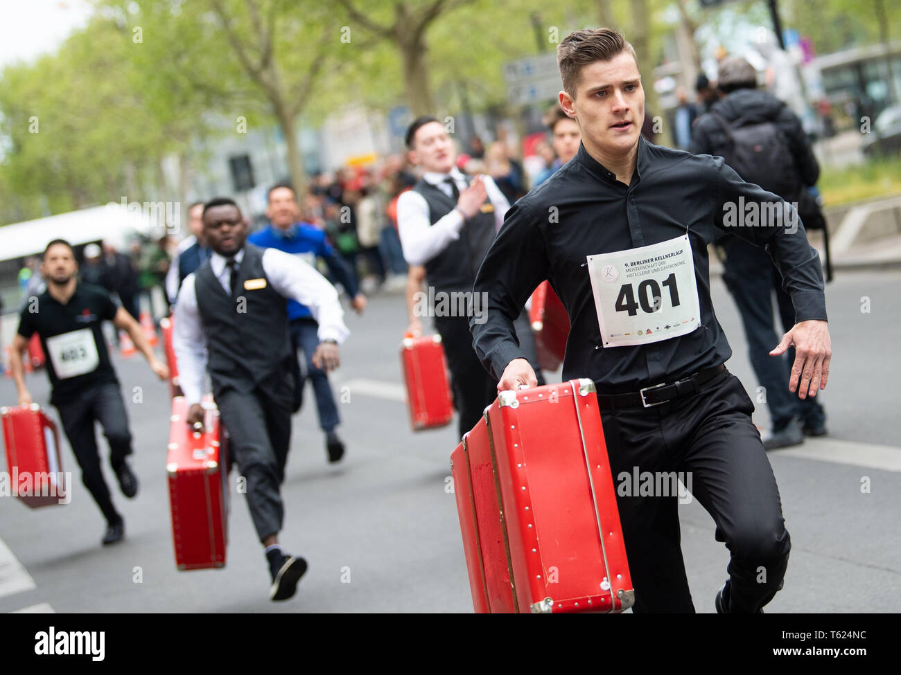 Berlin, Germany. 28th Apr, 2019. Pagen run past the spectators with filled suitcases at the 9th Berlin Waiter Run. Waiters, barkeepers, chefs and bellboys compete in the art of fast gastronomy. The 400 meter long running track is located on the one-sided closed Ku'damm. Credit: Monika Skolimowska/dpa-Zentralbild/dpa/Alamy Live News Stock Photo