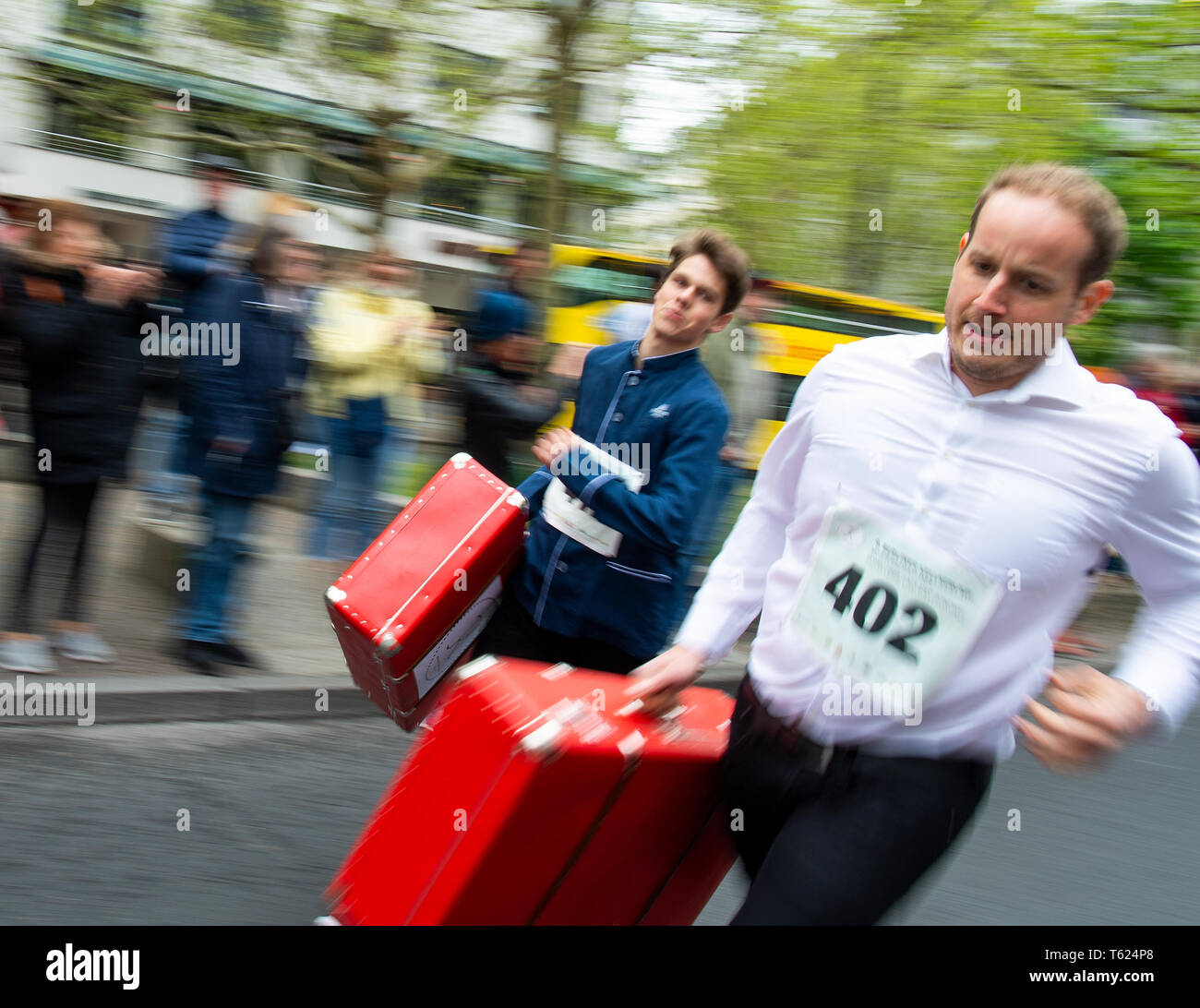 Berlin, Germany. 28th Apr, 2019. Two bellboys with filled suitcases pass the spectators at the 9th Berlin Waiter Run. Waiters, barkeepers, chefs and bellboys compete in the art of fast gastronomy. The 400 meter long running track is located on the one-sided closed Kudamm. Credit: Monika Skolimowska/dpa-Zentralbild/dpa/Alamy Live News Stock Photo