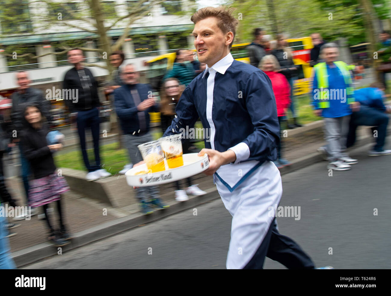 Berlin, Germany. 28th Apr, 2019. With a filled tray a waiter runs past the spectators at the 9th Berlin Waiter Run. Waiters, barkeepers, chefs and bellboys compete in the art of fast gastronomy. The 400 meter long running track is located on the one-sided closed Ku'damm. Credit: Monika Skolimowska/dpa-Zentralbild/dpa/Alamy Live News Stock Photo