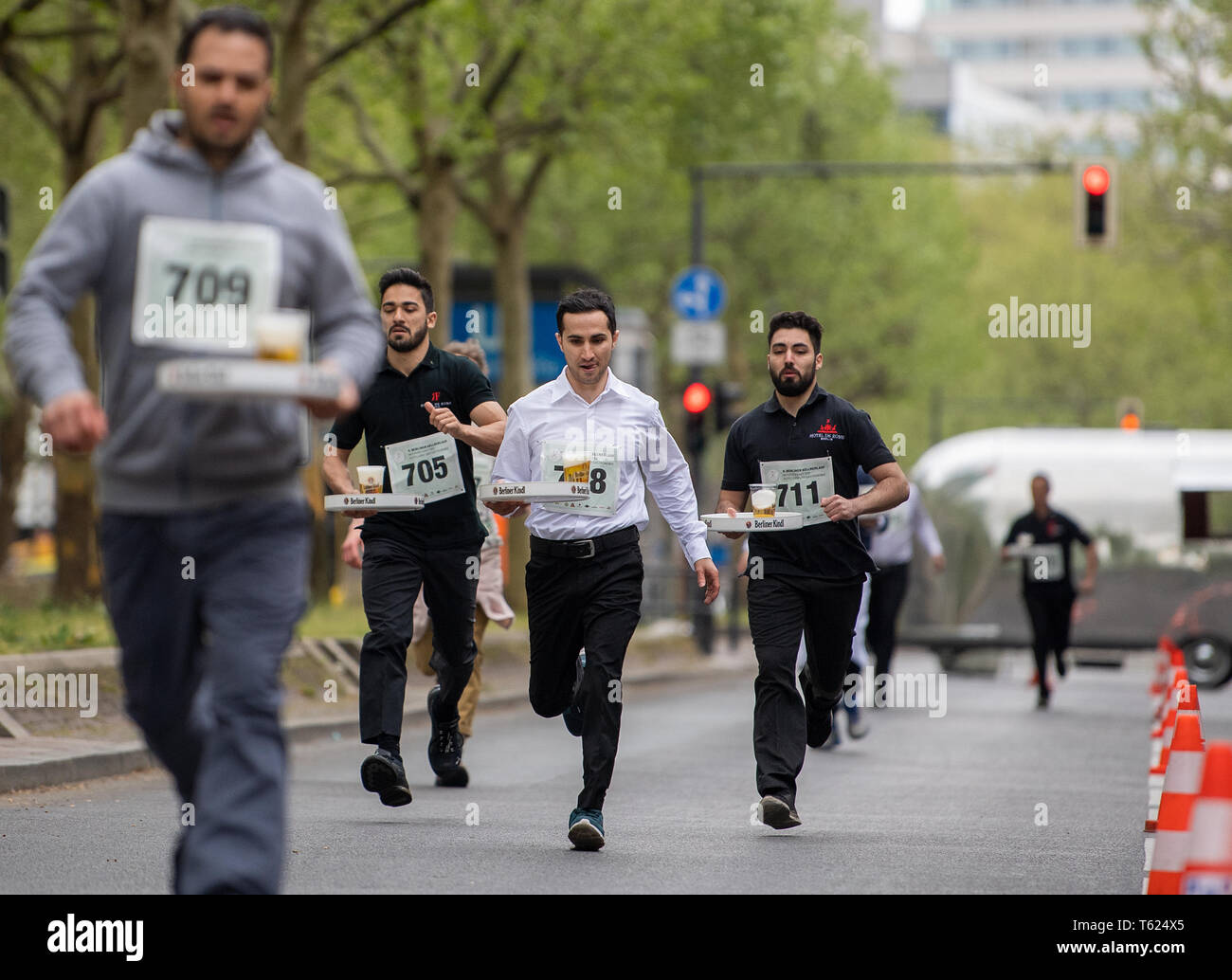 Berlin, Germany. 28th Apr, 2019. At the 9th Berliner Kellnerlauf, waiters walk across the Kurfürstendamm with filled trays. Waiters, barkeepers, chefs and bellboys compete in the art of fast gastronomy. The 400 meter long running track is located on the one-sided closed Ku'damm. Credit: Monika Skolimowska/dpa-Zentralbild/dpa/Alamy Live News Stock Photo