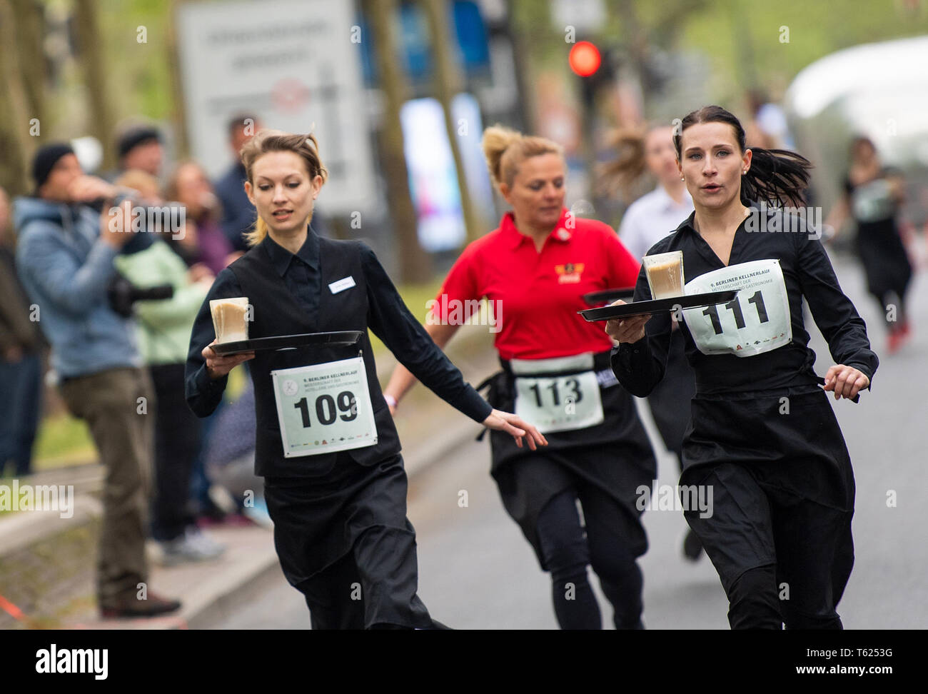Berlin, Germany. 28th Apr, 2019. Waitresses run past the spectators with filled tablets at the 9th Berlin Waiter Run. Waiters, barkeepers, chefs and bellboys compete in the art of fast gastronomy. The 400 meter long running track is located on the one-sided closed Ku'damm. Credit: Monika Skolimowska/dpa-Zentralbild/dpa/Alamy Live News Stock Photo