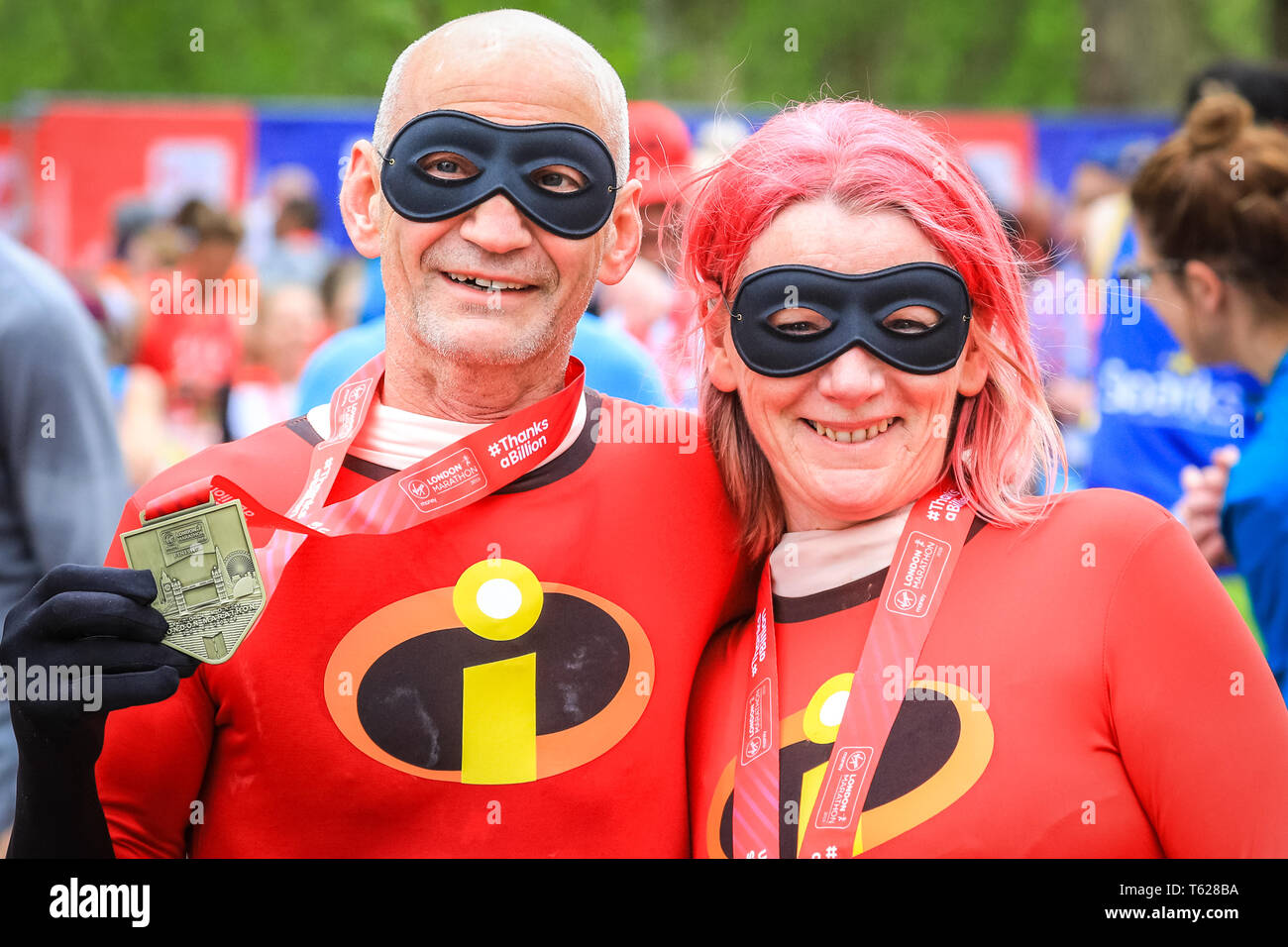 London, UK. 28th Apil 2019. Two superhero runners at the finish line. Over 40,000 starters are once again competing in the Virgin London Marathon, including those who take on the race for charities, in running clubs, in memory of loved ones and as personal lifetime goals. Credit: Imageplotter/Alamy Live News - Stock Image